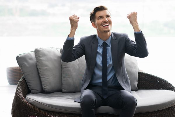Portrait of happy senior man sitting in cafe, raising his arms with joy